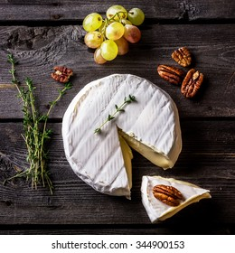 Cheese, herbs, nuts and green grape on dark wooden table. Overhead view. Selective fucus.