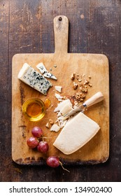 Cheese with honey, nuts and grapes on wooden cutting Board