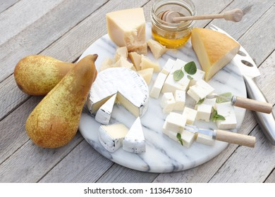 Cheese and honey on a marble board.