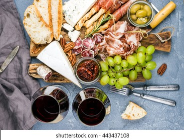 Cheese and meat appetizer selection. Prosciutto di Parma, salami, bread sticks, baguette slices, olives, sun-dried tomatoes, grapes and nutson rustic wooden board over grey concrete textured backdrop