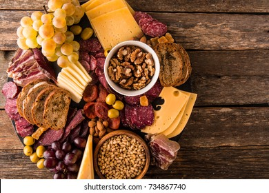 Cheese and meat appetizer selection. Prosciutto di Parma, salami, bread sticks, baguette slices, olives, grapes and nuts on rustic wooden background.