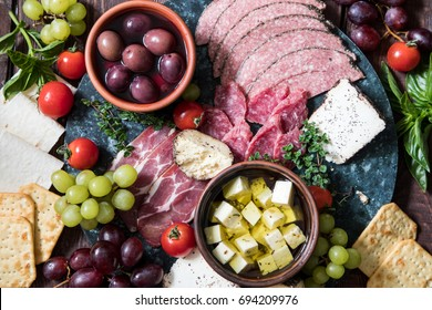 Cheese and meat appetizer selection. Variety of cheese, salami, prosciutto, bread, baguette, grapes, olives.
