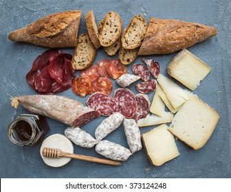 Cheese and meat appetizer selection or wine snack set. Variety of italian cheese, salami, bresaola, baguette and honey on over grey-blue concrete backdrop, top view