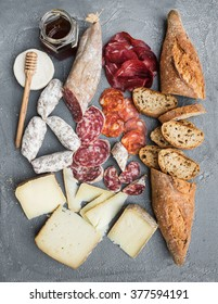 Cheese and meat appetizer selection or wine snack set. Variety of italian cheese, salami, bresaola, baguette and honey on over grey concrete backdrop, top view, vertical