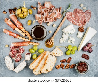 Cheese and meat appetizer selection or wine snack set. Variety of  cheese, salami, prosciutto, bread sticks, baguette, honey, grapes, olives, sun-dried tomatoes and pecan nuts over grey backdrop