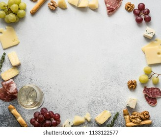 Cheese and meat  wine snack set frame. Variety of cheese, salami, prosciutto, bread sticks, grapes, walnut on grey background