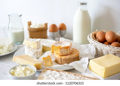 Cheese, milk, dairy products and eggs on rustic white wood background.