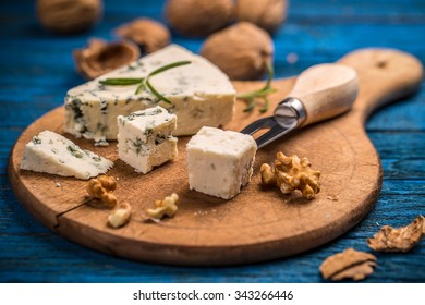 Cheese with mold on wooden cutting board
