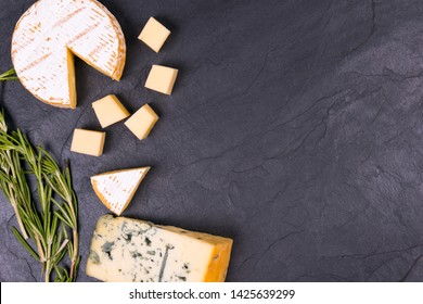 Cheese with mold with a sprig of thyme on a slate Board