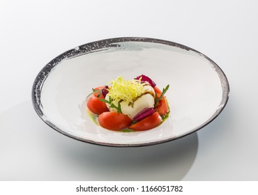 Cheese mozzarella with tomatoes and herbs in sauce on a plate isolated on white background.