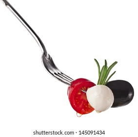 cheese mozzarella with vegetables on a fork close up isolated on white background
