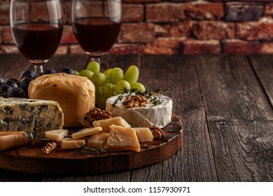 Cheese, nuts, grapes and red wine on wooden background, selective focus.