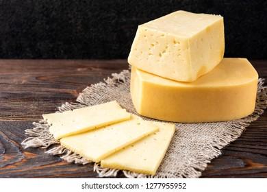 Cheese on dark wooden background.