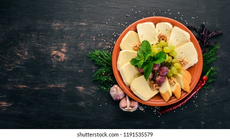 Cheese on a plate. Brynza and Suluguni cheese. On the old wooden background. Free space for text. Top view.