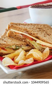 Cheese, onion and salad sandwich, served with crisps with a cup of coffee behind.