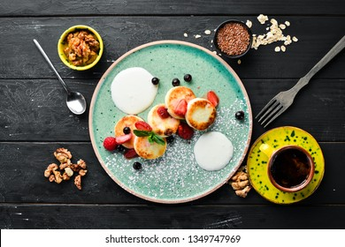 Cheese pancakes with strawberries and sour cream. Breakfast. In the plate. Top view. Flat lay composition Free copy space.