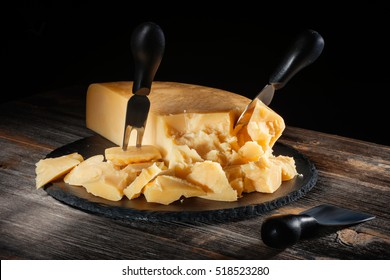 Cheese parmesan with a set of knives on  round slate board in style  rustic