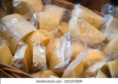 Cheese pieces in plastic package in shop close