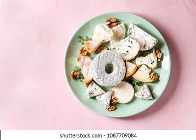 Cheese plate assortment of french cheese served with walnuts on turquoise ceramic plate over pink pastel background. Top view, space.