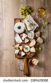 Cheese plate assortment of french cheese served with honey, walnuts, bread and grapes on rustic wooden serving board with glass of white wine over wood texture background. Top view, space.