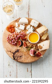 Cheese plate Assortment of various types of cheese on wooden cutting board