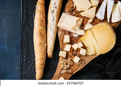 Cheese plate. Assortment of cheese with walnuts and bread on olive wood serving board with textile over black ornate and dark blue canvas as background. Top view with space.