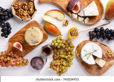 Cheese plate with blue cheese, brie, truffle hard cheese with grapes, figs, pears, honey, fruits and nuts on white table. Top view.