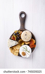 Cheese plate with blue cheese, brie, truffle hard cheese with grapes, figs, pears, honey, crackers, dried fruits and nuts on white table. Top view. Copy space.