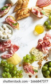 Cheese plate with brie, parmesan, cheddar and meat. Flatlay with gourmet snacks, fruits and baguette on marble board. Frame with copy space