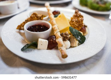 Cheese plate with cheeses Dorblu, Parmesan, Brie, Camembert and Roquefort in serving on the table