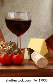 cheese plate with cherry tomatoes, bread and a glass of wine