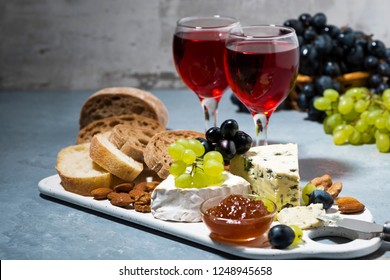 cheese plate, ciabatta, fresh grapes and two glasses of red wine, horizontal
