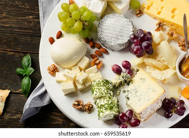 Cheese plate. Delicious cheese on a wooden table.