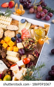 Cheese plate with delicious snacks. Christmas gift box with assorted cheese cubes, meat slices, fruits and nuts in gift box with crackers, olives and wine glass. Delicious charcuterie, copy space