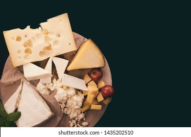 Cheese plate with different kinds of cheese (Emmental, Brie, cream cheese, Gouda, feta cheese) with green, flat on the black background without anyone of free space