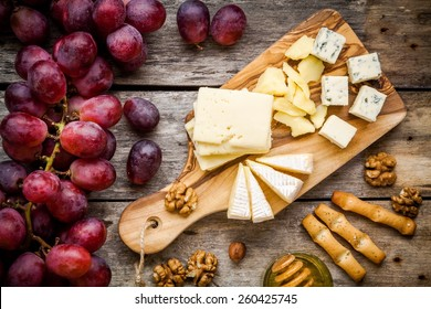 Cheese plate: Emmental, Camembert cheese, blue cheese, bread sticks, walnuts, hazelnuts, honey, grapes on wooden table