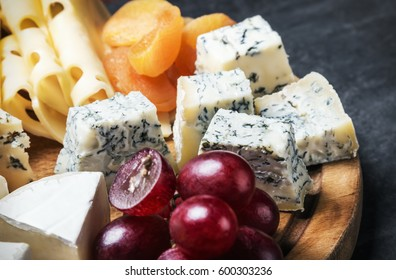 Cheese plate with fruits and nuts on a black background