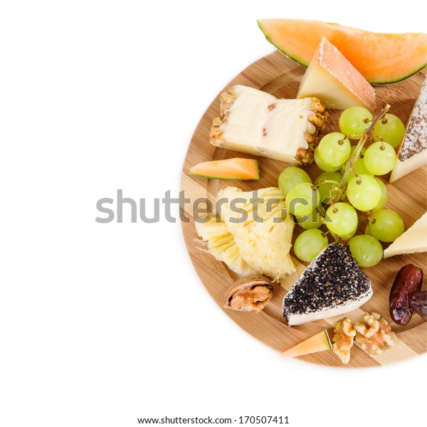 Cheese plate with grape and dry fruits. View from above, isolated, over white background with copy space.