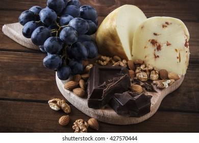 Plaque de fromage avec raisins, noix et chocolat sur une table en bois foncé