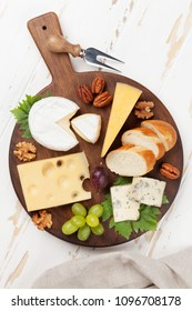 Cheese plate with grapes and nuts. Wine snaks. Top view
