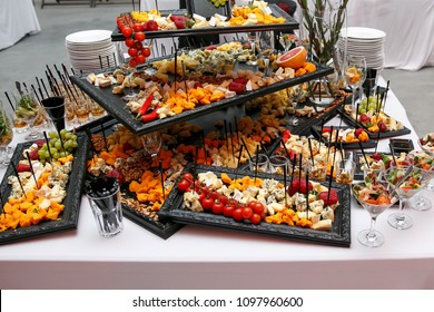 Cheese plate with onions and variety of appetizers on table on event catering
