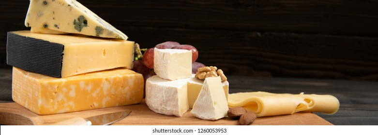Cheese plate: Parmesan, cheddar, gouda, camembert, brie,  and other with nuts on wooden board on dark background with place for text. Tasty appetizers. Top view. Copy space.