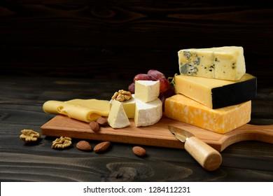 Käseplatte: Parmesan, Cheddar, Gouda, Camembert, Brie und andere mit Nüssen auf Holzbrett auf dunklem Hintergrund mit Platz für Text. Leckere Vorspeisen. Kopiert Platz.