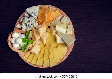 Cheese plate: Parmesan, cheddar, gouda, mozzarella and other with basil on wooden board on dark background with place for text. Tasty appetizers. Top view. Copy space.