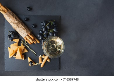 Cheese plate served with crackers, grapes and glass of white wine on dark background. Old gouda cheese on tasting plate. Flat lay with space for text.