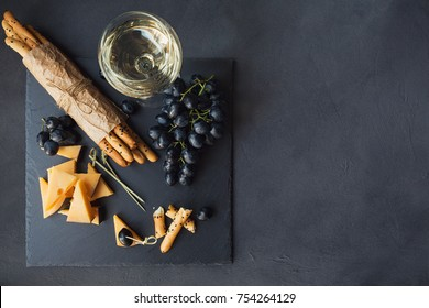 Cheese plate served with crackers, grapes and glass of white wine on dark background. Old gouda cheese on tasting plate. Top view with space for text.