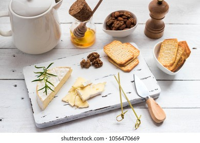 Cheese plate served with crackers, honey and nuts. Camembert on white wood serving board over white texture background. Appetizer theme. Top view