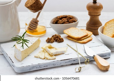 Cheese plate served with crackers, honey and nuts. Camembert on white wood serving board over white texture background. Appetizer theme.