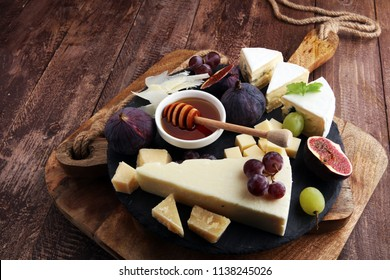 Cheese plate served with grapes, figs and honey on stone plate