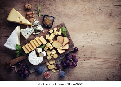 Cheese plate served with grapes, jam, figs, crackers and nuts on a wooden background